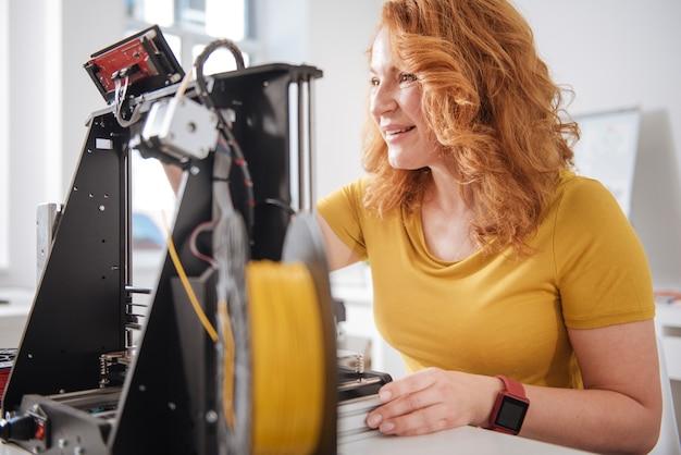 Radosna, szczęśliwa miła kobieta siedząca przy stole i pracująca z technologiami 3d podczas opracowywania nowego projektu