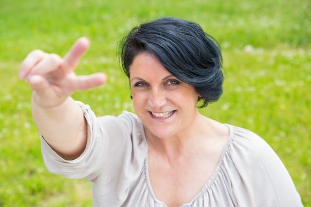 Radosna szczęśliwa w średnim wieku kobieta pokazuje pokoju znaka