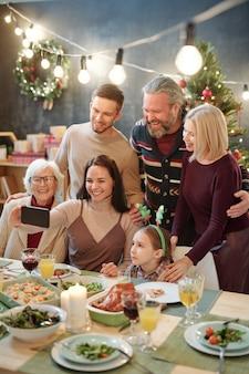 Radosna sześcioosobowa rodzina patrzy na smartfona trzymanego przez młodą kobietę podczas robienia selfie przy świątecznym stole w domu