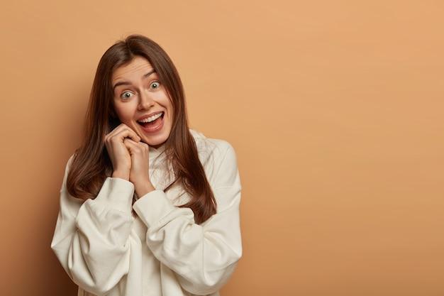 Radosna, urocza kobieta wygłupia się z przyjaciółmi, pozytywnie patrzy na aparat, trzyma ręce blisko twarzy, przechyla głowę, nosi zwykłą białą bluzę z kapturem, otwiera usta