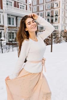 Radosna, urocza młoda kobieta w białym wełnianym swetrze i jasnobeżowej spódnicy, ciesząca się mroźną zimową pogodą. pora śniegu, okazywanie błyskotliwych pozytywnych emocji, mróz, uśmiech.