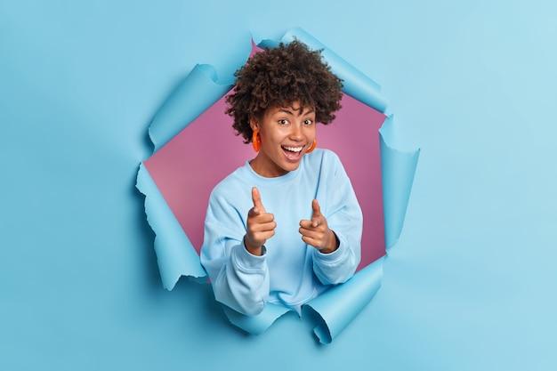 Radosna uśmiechnięta ciemnoskóra afro american kobieta wskazuje palcem wskazującym na aparat