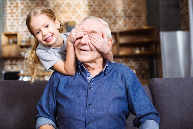 Radosna uśmiechnięta dziewczynka zamykająca oczy dziadka podczas grania w grę