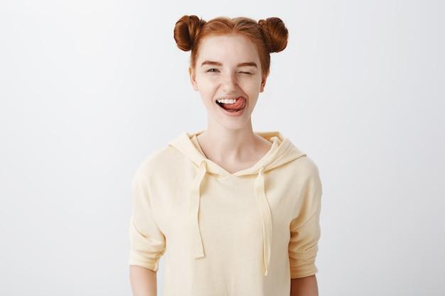 Radosna, uśmiechnięta ruda dziewczyna mruga i pokazuje język