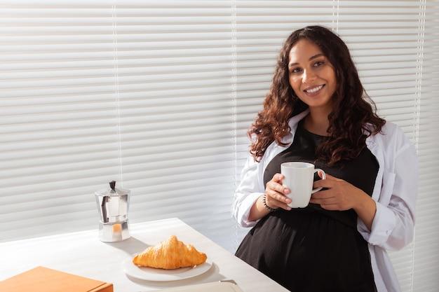 Radosna w ciąży młoda piękna kobieta patrzy na aparat podczas porannego śniadania z kawą