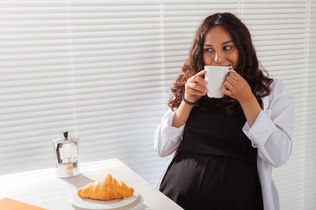Radosna w ciąży młoda piękna kobieta patrzy przez żaluzje podczas porannego śniadania z kawą