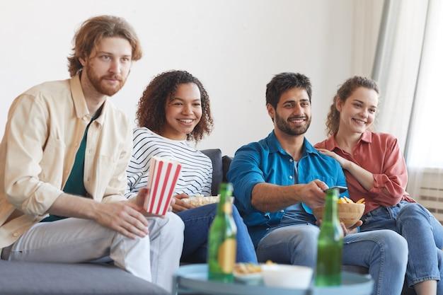Radosna wieloetniczna grupa przyjaciół, którzy razem oglądają telewizję, siedząc na wygodnej kanapie w domu i jedząc przekąski