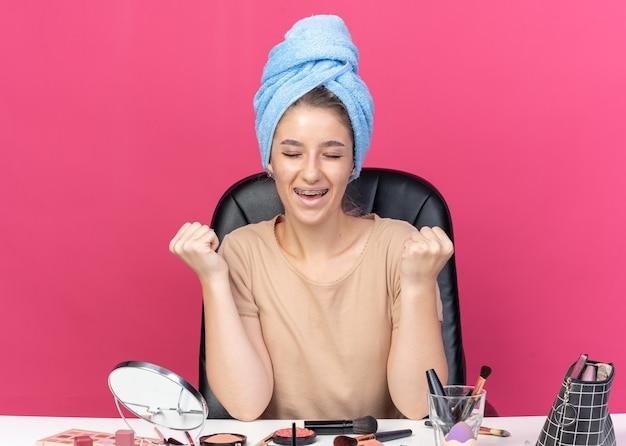 Radosna z zamkniętymi oczami młoda piękna dziewczyna nosząca aparat ortodontyczny siedzi przy stole z narzędziami do makijażu owiniętymi włosami w ręcznik pokazujący gest tak na różowej ścianie