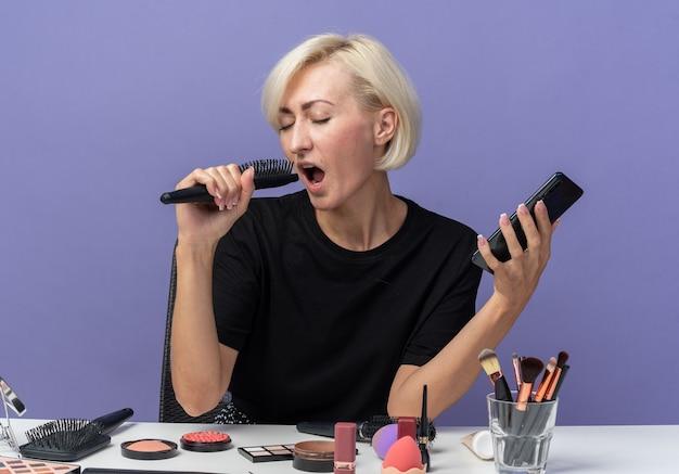 Radosna z zamkniętymi oczami młoda piękna dziewczyna siedzi przy stole z narzędziami do makijażu, trzymając telefon z grzebieniem i śpiewając na niebieskiej ścianie