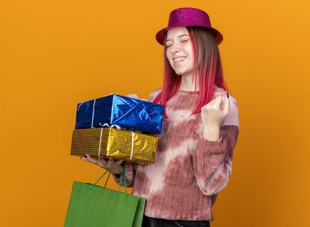 Radosna z zamkniętymi oczami młoda piękna dziewczyna w imprezowym kapeluszu trzymająca torbę na prezenty z pudełkami prezentowymi pokazującymi gest