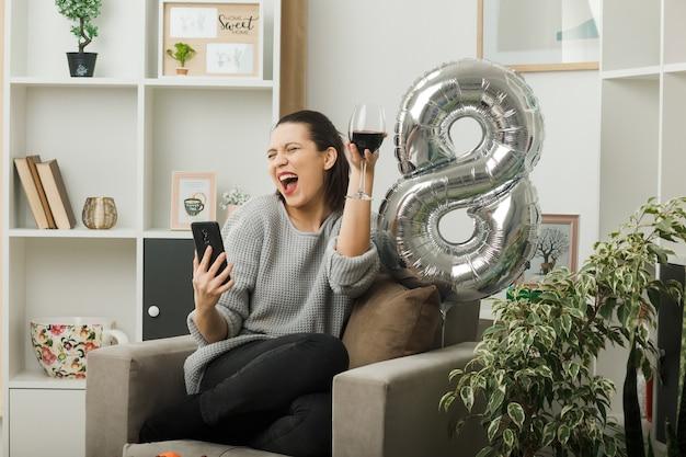 Radosna z zamkniętymi oczami piękna dziewczyna w szczęśliwy dzień kobiet trzymająca kieliszek wina weź selfie siedząc na fotelu w salonie