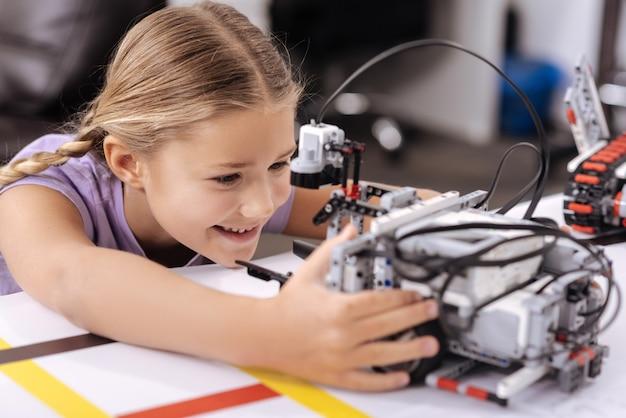 Radosna zabawka techniczna. zachwycona, zainspirowana szczęśliwa dziewczyna siedząca w laboratorium robotyki i patrząc na cyber-robota, wyrażająca pozytywne nastawienie