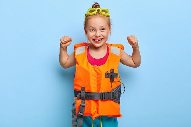 Radosna zabawna dziewczyna o rudych włosach uczesanych w kok, unosi ramiona i pokazuje mięśnie