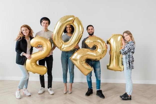Radosne chłopaki i dziewczyny w codziennych ubraniach stoją na podłodze przy ścianie i pokazują numer na następny rok