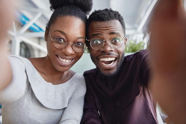 Radosne czarne przyjaciółki i przyjaciele bawią się razem, robią sobie zdjęcia lub pozują do selfie, będąc w dobrym nastroju po udanym dniu.