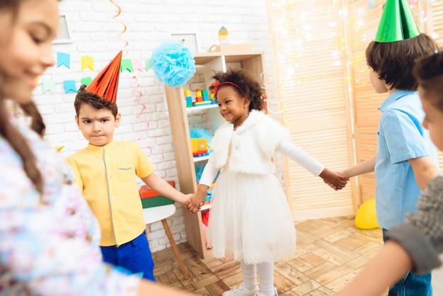 Radosne dzieci tańczą okrągły taniec na przyjęciu urodzinowym.