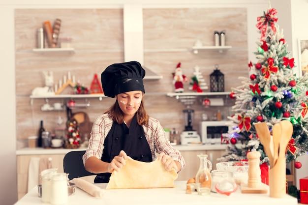 Radosne dziecko bawiące się ciastem w boże narodzenie w fartuchu