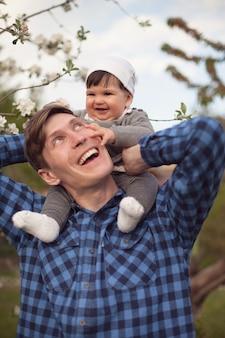 Radosne dziecko siedzi na ramionach taty na tle białych kwiatów jabłoni.