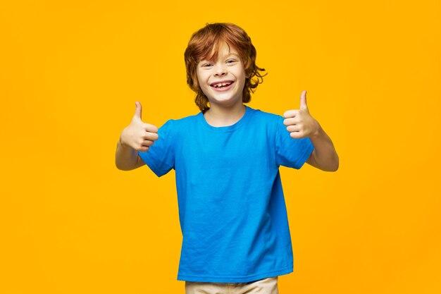 Radosne dziecko w niebieskiej koszulce pokazuje kciuk i bawi się