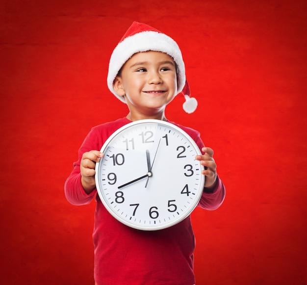 Radosne dziecko z christmas kapelusz i wielkim zegarem