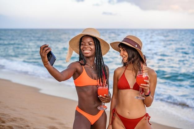 Radosne dziewczyny ze smartfonem robiące selfie na plaży
