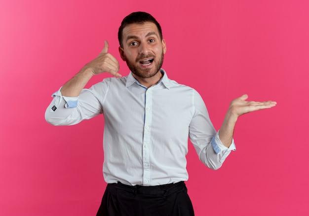 Radosne gesty przystojnego mężczyzny nazywają mnie ręką znak trzyma pustą dłoń otwartą na białym tle na różowej ścianie