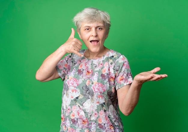 Radosne gesty starszej kobiety nazywają mnie podpisem i trzyma dłoń pustą na białym tle na zielonej ścianie