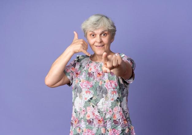 Radosne gesty starszej kobiety nazywają mnie znakiem i wskazuje na fioletowej ścianie