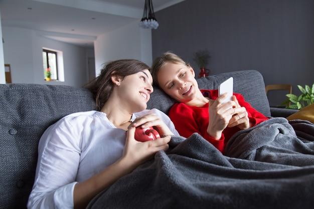 Radosne homoseksualne dziewczyny odpoczywają na kanapie