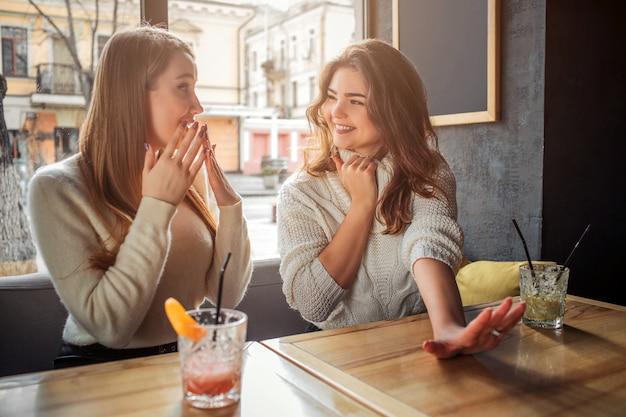 Radosne i szczęśliwe młode kobiety siedzą przy stole. pierwsza ręka pokazowa. inny model się zastanawia. oni są szczęśliwi.