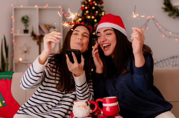 Radosne ładne młode dziewczyny w okularach reniferów i czapce świętego mikołaja trzymają ognie i patrzą na telefon siedzący na fotelach i cieszący się świątecznym czasem w domu