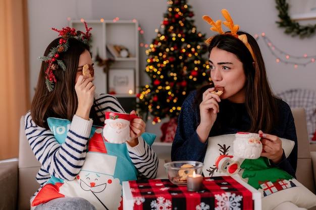 Radosne ładne młode dziewczyny z wieńcem ostrokrzewu i opaską renifera trzymają kubki i jedzą ciastka siedząc na fotelach i ciesząc się świętami w domu