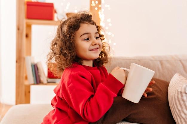 Radosne małe dziecko pije herbatę. śliczne kręcone dziecko trzyma kubek.