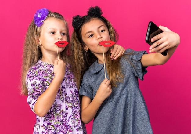 Radosne małe ładne dziewczyny trzymające sztuczne usta na kijach robiące selfie odizolowane na różowej ścianie z kopią miejsca