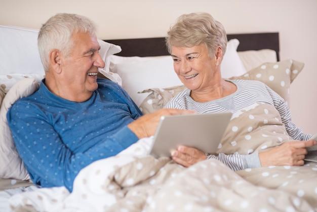 Radosne małżeństwo seniorów razem przy użyciu tabletu