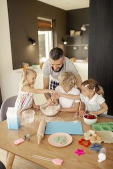 Radosne, miłe dzieci pomagają sobie w kuchni