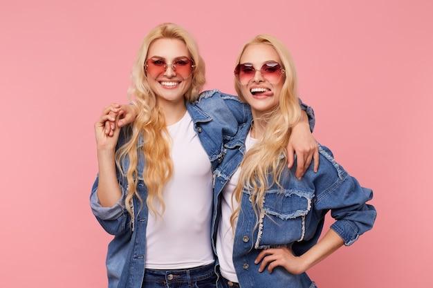 Radosne młode dość długowłose blond siostry w czerwonych okularach przeciwsłonecznych obejmujących i szczęśliwie patrząc na kamerę z szerokimi uśmiechami, odizolowane na różowym tle