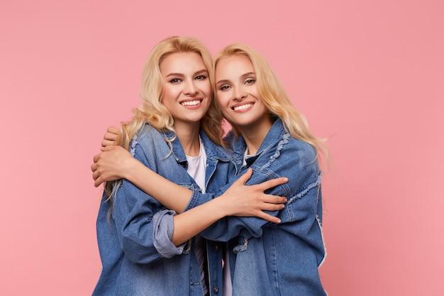 Radosne młode urocze blond siostry z falującą fryzurą delikatnie przytulają się do siebie, patrząc z radością w kamerę z przyjemnymi uśmiechami, odizolowane na różowym tle