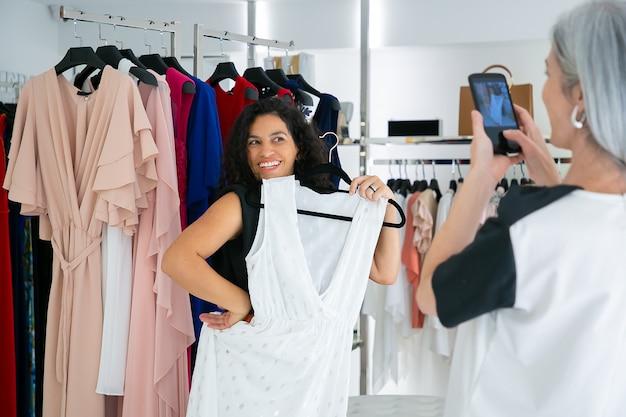 Radosne panie spędzające razem czas na zakupach w butiku, trzymając sukienki, bawiąc się i robiąc zdjęcia telefonem komórkowym. koncepcja konsumpcjonizmu lub zakupów
