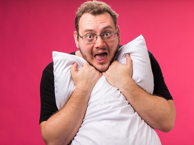 Radosne patrzenie na aparat w średnim wieku chory mężczyzna przytulił poduszkę