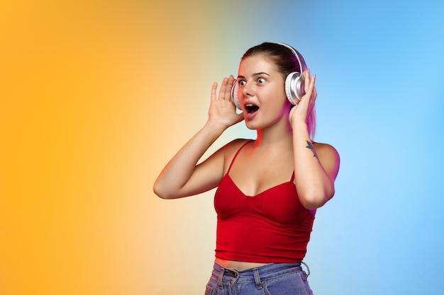 Radosne słuchanie muzyki portret młodej kobiety rasy kaukaskiej w studio gradientowym
