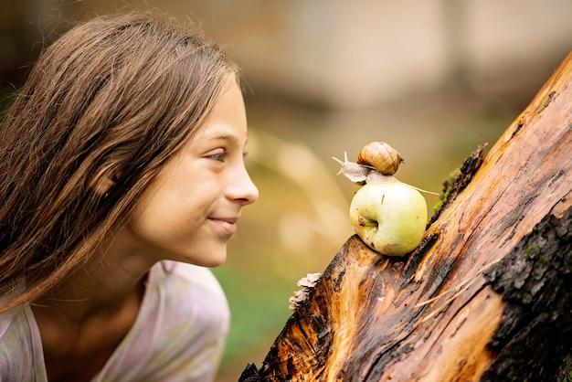 Radosne spotkanie małej dziewczynki i ślimaka. letnie zdjęcie w deszczu.