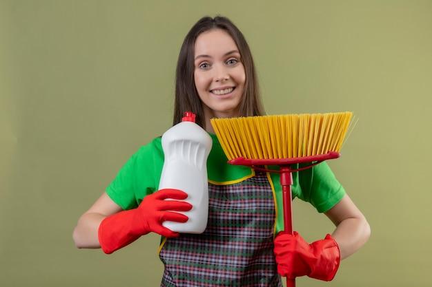 Radosne sprzątanie młoda kobieta ubrana w mundur w czerwonych rękawiczkach trzyma mop ze środkiem czyszczącym na odizolowanej zielonej ścianie