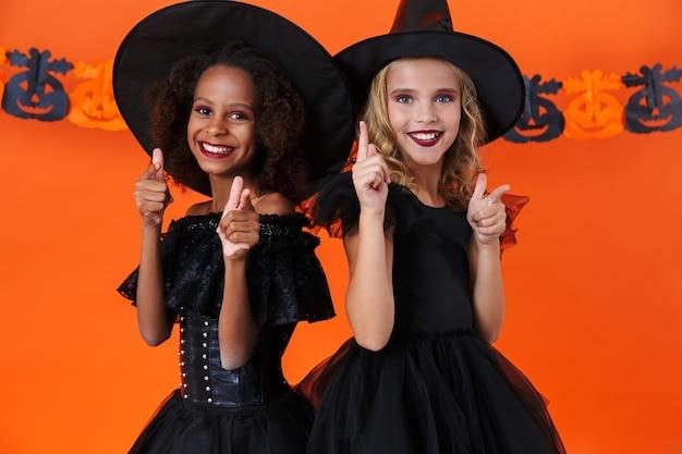 Radosne, wielonarodowe dziewczyny w czarnych kostiumach na halloween, patrzące i wskazujące palcami na aparat, odizolowane na pomarańczowej ścianie z dyni
