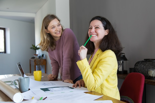 Radośni architekci dyskutuje domowego projekt przy biurkiem