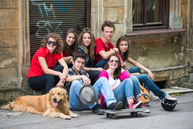 Radośni młodzi ludzie siedzi na ulicie