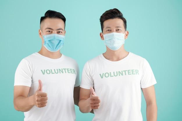 Radosni młodzi mężczyźni w maskach ochronnych pracujący jako wolontariusze podczas pandemii covid-19
