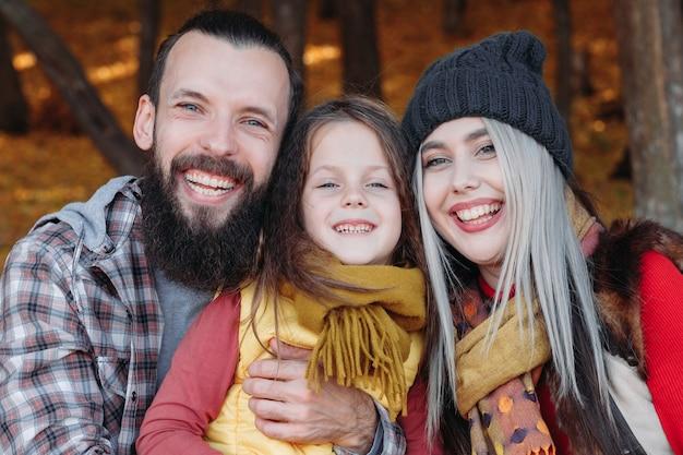 Radośni młodzi rodzice spędzają czas z córką w lesie