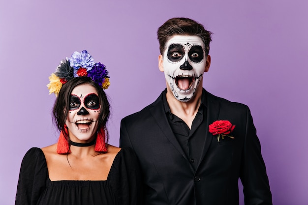 Radośni, niegrzeczni mężczyźni i kobiety w czarnych ubraniach z czerwonymi detalami krzyczą ze zdumienia, pozując do portretu z halloweenowym makijażem.
