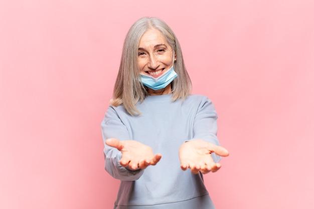 Radośnie uśmiechnięta kobieta w średnim wieku z przyjaznym, pewnym siebie, pozytywnym spojrzeniem, oferująca i pokazująca przedmiot lub koncepcję